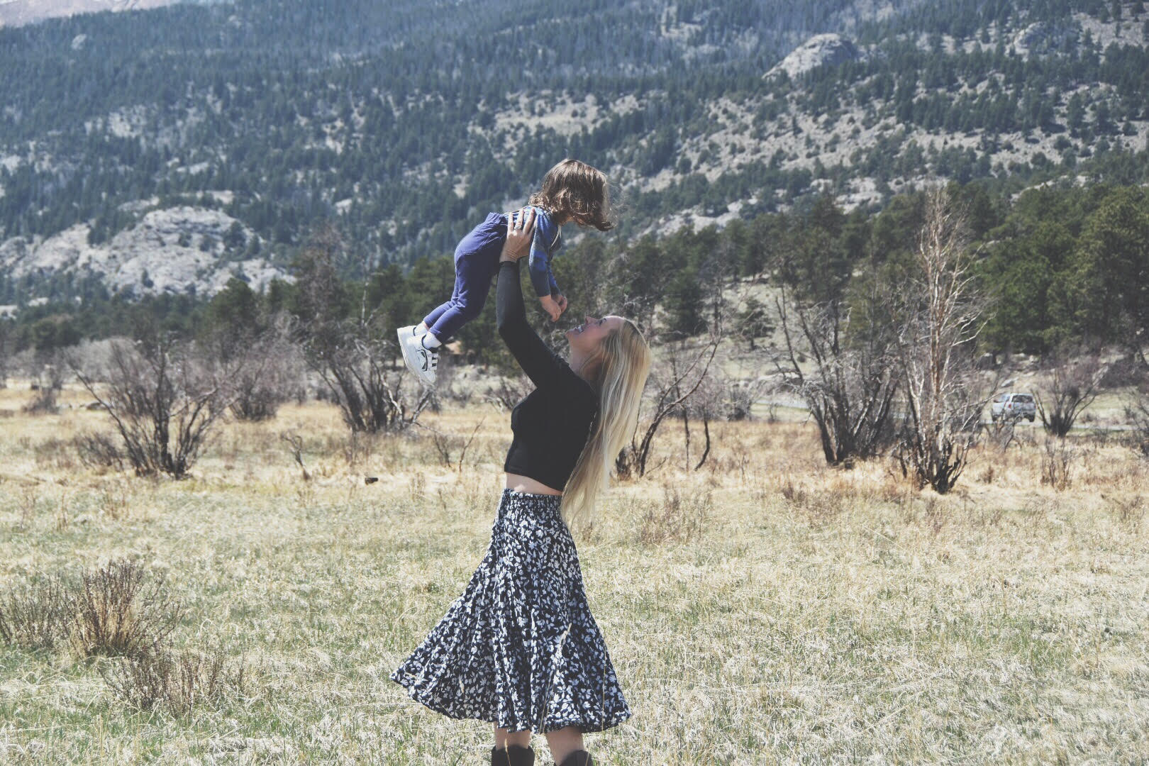 Mama and Child dance in front of mountains