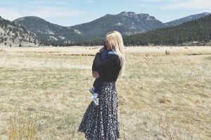 Mama and Child hug in front of mountains