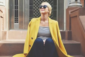 Chondra Sanchez in yellow Lafayette 148 coat on stoop