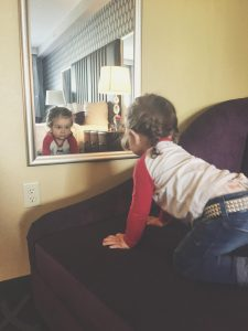 toddler looks in mirror in studded belt